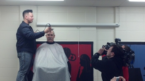 Spike, the Barber, shaving 6th grade teacher Justin Miller hair. .