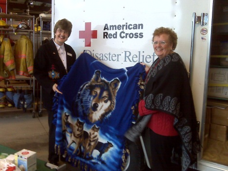 Mary Preston, from Kohls, presents Disaster Action Team member, Vicki Jenks with blankets a few years ago at an event.