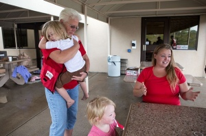 Monday, September 16, 2013. Red Cross Shelter at Thompson School, Loveland, CO. Red Cross Health Services worker Pam Robinson, RN, of Masonville, Colorado, hugs Adalynn Oft, 4, of Drake, Colorado, as her sister, Zoee, 1, looks on and her mother Charlsey, share their story.  Photo by Hector Emanuel/American Red Cross