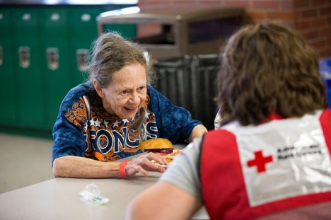 Monday, September 16, 2013. Red Cross shelter at Niwot High School, Niwot, Colorado. Donna Hitz, 81, of Lyons, Colorado, shares with Red Cross worker Jody Weyers of Green Bay, Wisconsin, her experience of being airlifted by a helicopter from her property to safety. Her neighbors knocked on her door to alert her to the evacuation and the next thing she knew, a helicopter was landing in her pasture. Photo by Hector Emanuel/American Red Cross