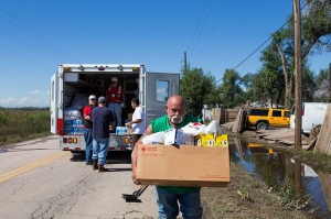 Tuesday, September 17, 2013. 49th St. in Evans, Colorado. American Red Cross emergency response drivers, Dennis Pierce from Louisburg, Kansas and Dustin Dunkin, of Garnett, Kansas handing out supplies to Robert Lujan and Brian Mestas of Evans, Colorado. Bernie Lujan of Evans, Colorado taking a box of supplies including masks, garbage bags, and paper towels to assist with flood relief cleanup to his home. Photo by Hector Emanuel/American Red Cross