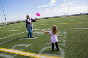 "Monday, September 16, 2013. Red Cross shelter at Mead High School, Mead, CO. Red Cross Shelter Manager, Ruth ""Max"" Bourke, of Ault, Colorado, plays catch with JoAnn Hammond, 5, of Del Camino, Colorado. Photo by Hector Emanuel/American Red Cross"
