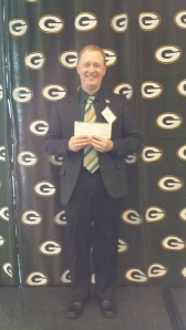 John Kost, Service to the Armed Forces Regional Director, holding the check at the awards luncheon on December 17, 2013
