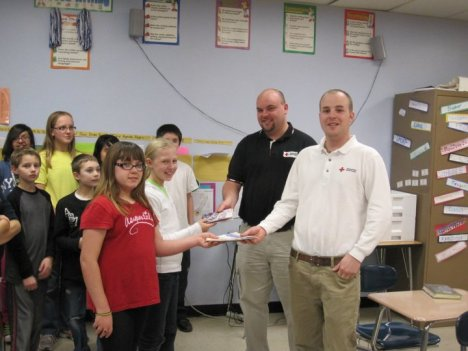 Kayleigh Kaminski and Kaylee Kuhn are seen handing over the greeting cards to Nick Cluppert (left) and Paul Fruit, from the Red Cross