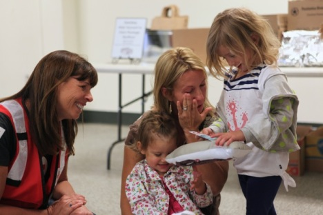 American Red Cross volunteer Mar Tobiason presents Hug-A-Hero dolls to the Blankenship family.  Lillie (3 ½) and Hallie (2) along with their mother Katherine Blankenship were delighted with tears of joy.