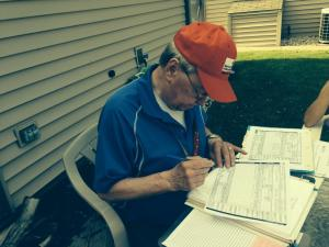 Disaster Volunteer, Dick Henderson, writing out our forms to assist clients in need.