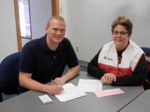 Travis Waack, Regional Manager, Direct Services, working with Kathy Schuh-Ries in filling out her deployment paperwork.